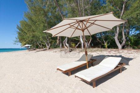 Photo pour Chaises longues et parasol sur la plage de sable blanc, face au lagon - image libre de droit