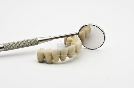 Photo pour Prothèses dentaires avec miroir dentaire sur fond blanc - image libre de droit