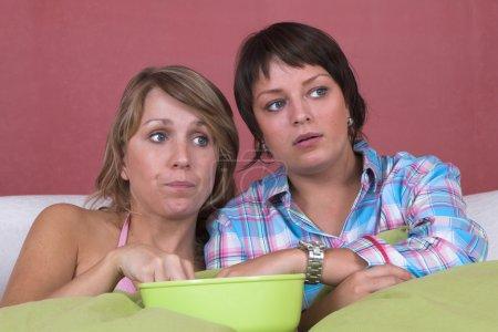 Photo pour Deux filles regardant un film ; l'une a l'air très intéressée, l'autre pas tellement - image libre de droit