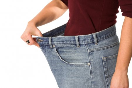 Photo for Female showing how much weight she has lost by wearing her old jeans that are sizes too big - Royalty Free Image