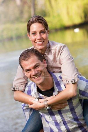 Photo pour Beau jeune couple s'amusant à faire une balade en dos de porc - image libre de droit
