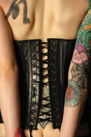 Photo for A young slim women with arm and back tattoos dressed in a black leather corset. Focus is on the middle of corset. - Royalty Free Image