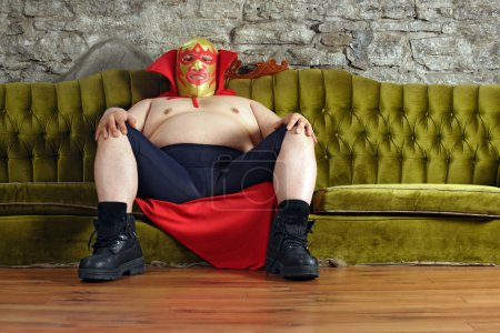 Photo for Photograph of a Mexican wrestler or Luchador sitting on a green couch waiting for his match to begin. - Royalty Free Image