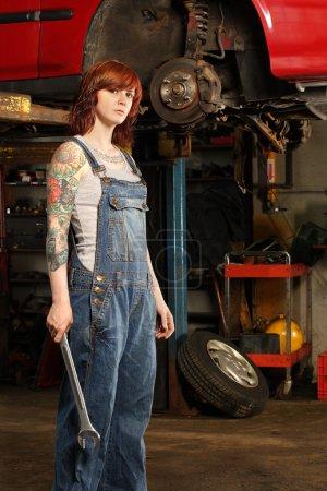 Foto de Foto de un mecánico joven hermosa pelirroja vistiendo guardapolvos y sosteniendo una enorme llave. propiedad adjunta comunicado es para brazo tatuajes. - Imagen libre de derechos
