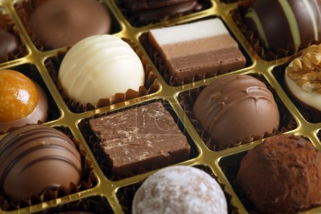 Photo for A small assortment of chocolate truffles and pralines in a box. Very Shallow depth of field, focusing across the middle. - Royalty Free Image