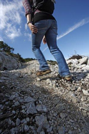 Photo pour Photo d'une femme active avec sac à dos de randonnée jusqu'à un sentier de montagne. flou de mouvement sur la majeure partie de l'image sauf autour de chaussure droite. - image libre de droit
