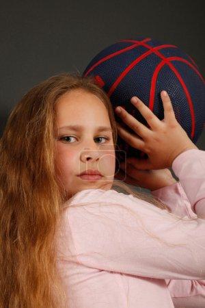 Young girl play with a basketball ball