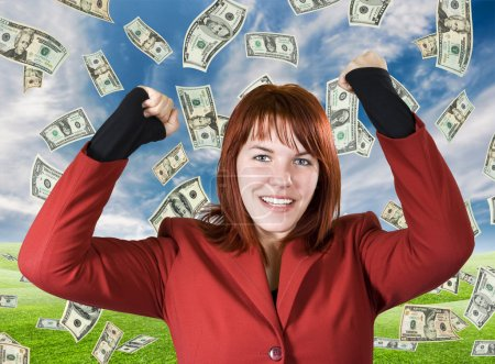 Photo for Cute girl with red hair dressed in a red business dress with her arms raised smiling and rejoicing for a win. Dollars falling from a beautiful blue sky. - Royalty Free Image