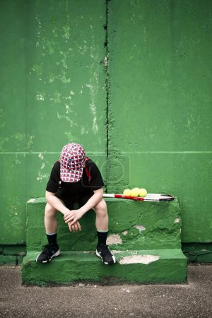 Photo for Sad tennis player having rest in front of old training wall - Royalty Free Image