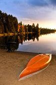 Lake sunset with canoe on beach