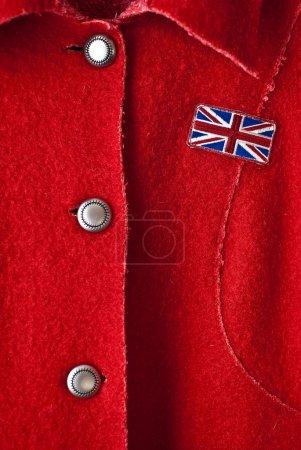 Photo pour Closeup manteau rouge avec le drapeau de la Grande-Bretagne et l'ornement sur les boutons. - image libre de droit