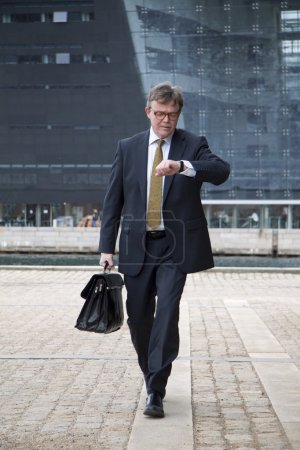 Photo for Well dressed walking businessman looking at his wristwatch, carries briefcase - Royalty Free Image