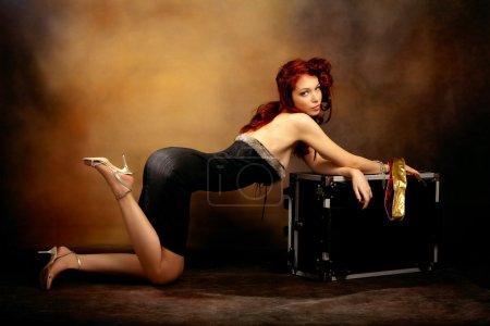 Photo pour Femme belle chevelure rousse en robe sexy se pencha sur le tronc, studio tourné - image libre de droit