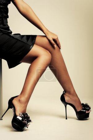 Photo for Beautiful tanned female lags in high heels, studio shot - Royalty Free Image
