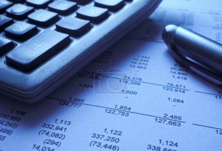 Photo pour Gros plan d'une calculatrice et stylo au sommet des États financiers - image libre de droit
