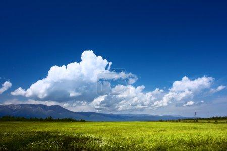 Photo pour Montagnes vallée et bleu ciel avec nuages duveteux - image libre de droit