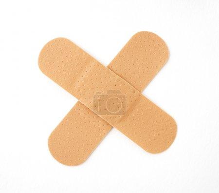 Photo pour Deux plâtres de friction formant une croix isolée sur blanc - image libre de droit