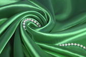 Pearl beads on green silk