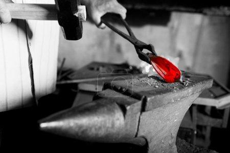 Blacksmith in the smithy manufactures decorative e...