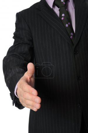 Man in a suit holds out his hand for a handshake.