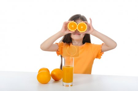 Girl at the table with oranges and juice.