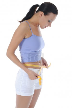 Young athletic girl measuring waist.
