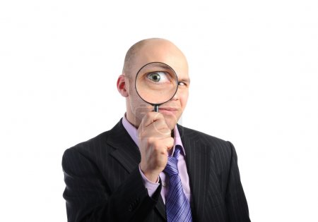 Businessman looking through a magnifying