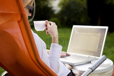 Photo for Young woman working outside on computer and drinking coffee - Royalty Free Image