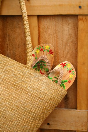 Pair of sandals hanging out of wicker purse