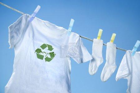 Photo pour T-shirt avec logo de recyclage séchage sur corde à linge - image libre de droit