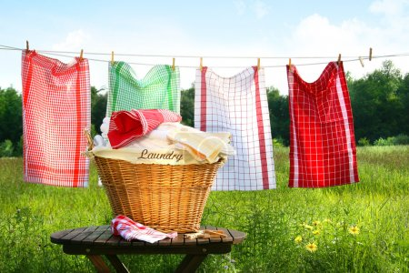 Towels drying on the clothesline with laundry bask...