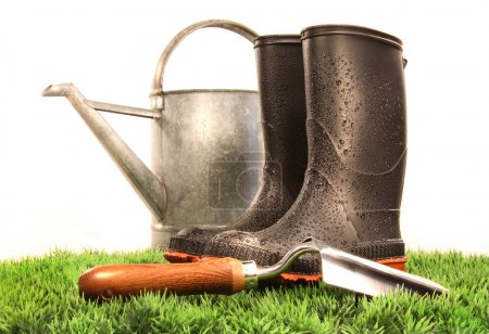 Photo for Garden boots with tool and watering can on grass - Royalty Free Image