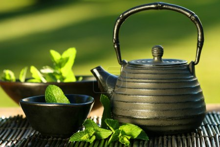 Photo for Black iron asian teapot with sprigs of mint for tea - Royalty Free Image