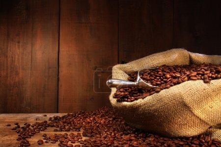 Photo pour Sac de toile de jute de grains de café sur fond de bois sombre - image libre de droit