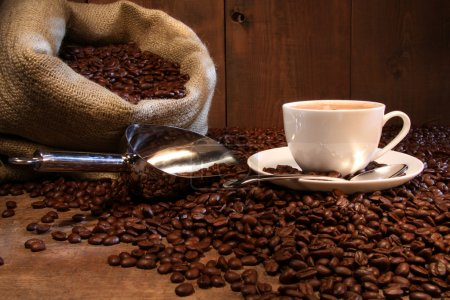 Photo for Coffee cup with burlap sack of roasted beans on rustic table - Royalty Free Image