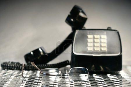Photo pour Noir téléphone vintage avec une paire de lunettes de lecture - image libre de droit