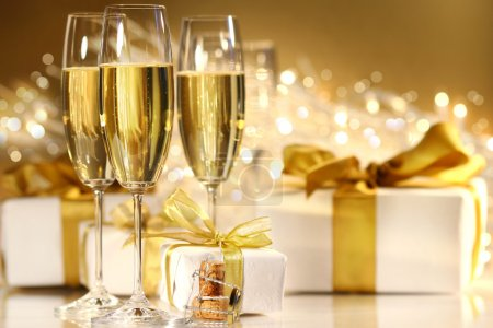 Photo for Glasses of champagne with gold ribbon gifts - Royalty Free Image