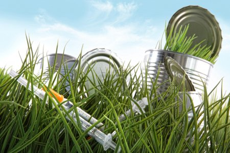 Photo for Syringe needles and food cans left in the grass with blue sky - Royalty Free Image