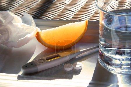 Photo pour Tissu, coin orange, verre d'eau, thermomètre et pilules contre le rhume pour soulager les symptômes de la grippe - image libre de droit