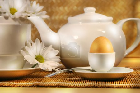 Photo for Tea cup and teapot with egg and daisy on the table - Royalty Free Image
