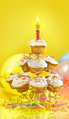 Photo pour Beaucoup de cupcakes sur un stand à plusieurs niveaux sur fond jaune - image libre de droit