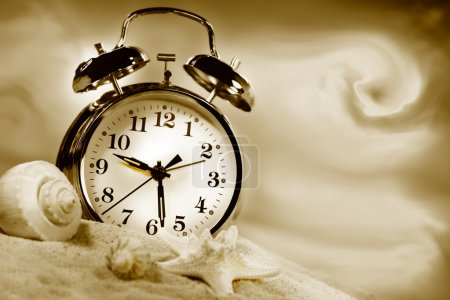 Photo for Alarm clock showing time on the beach with seashells/Sepia tone - Royalty Free Image