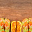 Brightly colored flip-flops on wood deck...
