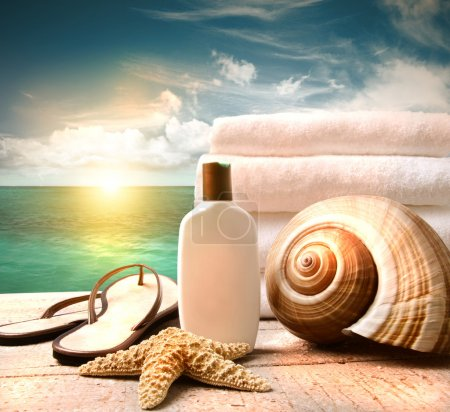 Photo for Sunblock lotion and white towels with ocean scene - Royalty Free Image