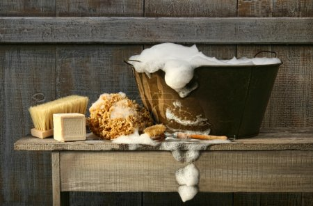 Photo pour Vieille baignoire avec savon sur banc rustique - image libre de droit
