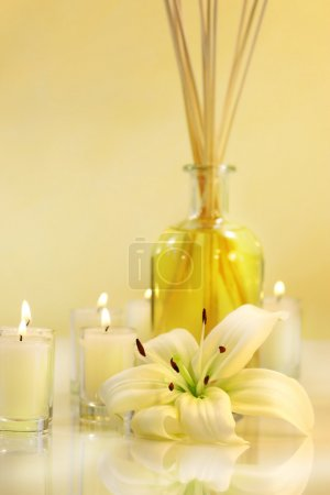 Photo for Scented sticks with candles and lily on pale background - Royalty Free Image