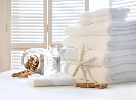 Photo for Fluffy white towels on table with shutter doors - Royalty Free Image