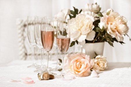 Photo pour Deux verres remplis de champagne rose avec des fleurs - image libre de droit