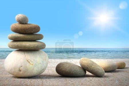 Photo pour Pile de roches de spa sur bois contre l'eau et le ciel bleu - image libre de droit