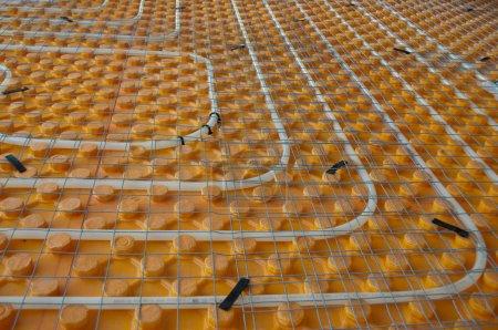 Photo pour Tube de chauffage par le sol orange posé sur un chantier - image libre de droit